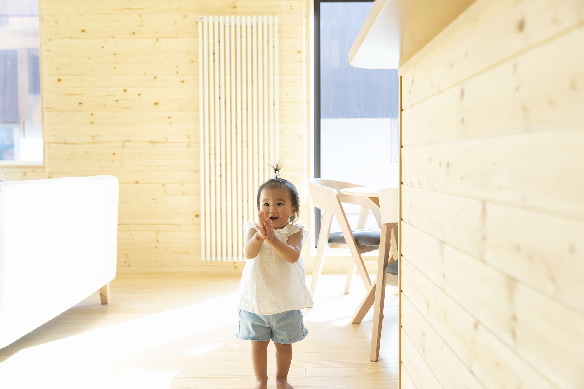 - 木の壁が光をやわらげる室内は、ムクの床からも自然の温もりを感じられる優しいデザイン。娘さんも踊ったり、歌ったりとゴキゲン。 -  -