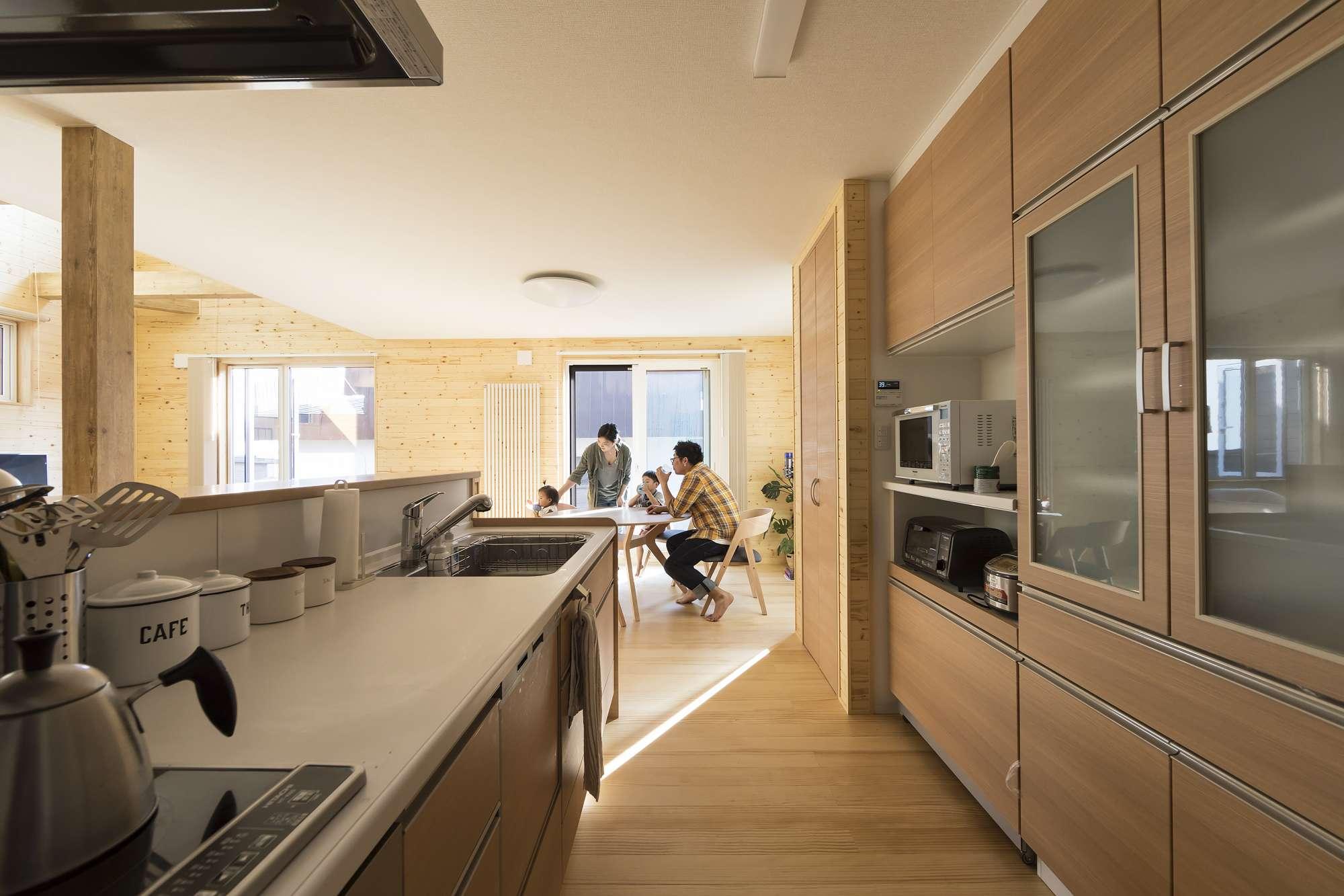 キッチン - 室内のデザインに合わせて木調のパネルにしたキッチン。リビングに来客があるときに、キッチンの中を隠せるパーテーションを造作。パントリーもあるので、4人家族の食材や生活用品をストックできます。 -  -